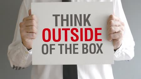 düşünürken : Businessman holding paper with Think Outside of the Box title. Creativity in business concept.