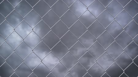 цепь : Chain link wire fence against cloudy sky time lapse