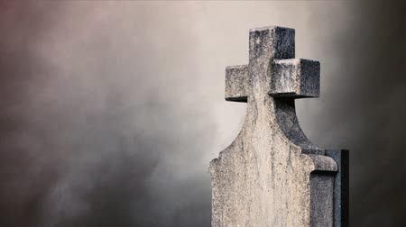 temető : Cross on the cemetery. Time lapse clouds flowing past a stone cross on a graveyard.
