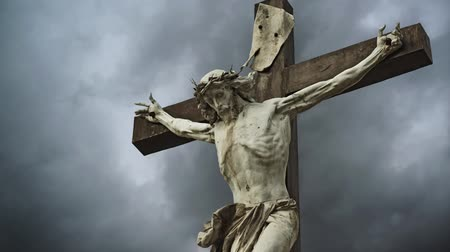 christian : Crucifixion. Christian cross with Jesus Christ statue over stormy clouds time lapse. Stock Footage
