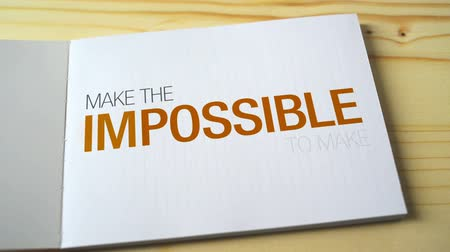 motivasyonel : Impossible becomes possible by fading letters printed on the notebook page. 1920x1080 full hd footage.
