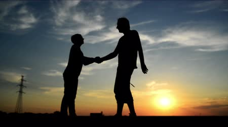 üdvözlettel : Man meeting woman on the street in sunset and greeting her with a warm handshake.