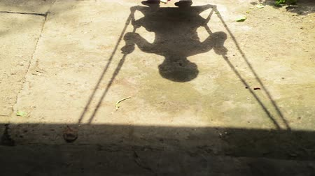 houpavý : Shadow of unrecognizable boy child on a swing seat in summer afternoon. 1920x0180 full hd footage.