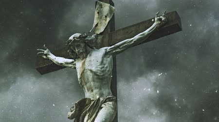 ježíš : Crucifixion cross with Jesus Christ statue over stormy clouds and Snow falling time lapse as Religious Christian Concept.