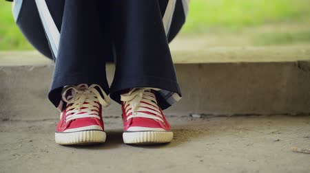 musluk : Young Teenage Woman in Red Sneakers Tapping Feet and Waiting for Someone while Sitting on Concrete Block in Urban Environment. Stok Video