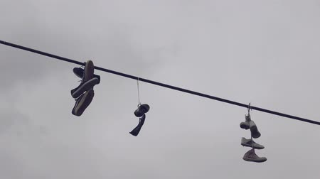 kable : Shoe Tossing, Old Sneakers Hanging on Power Line Wire, Urban Scenery