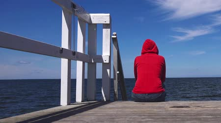 одиноко : Alone Young Woman in Red Hooded Shirt Sitting at the Edge of Wooden Pier Looking at Water - Hopelessness, Solitude, Alienation Concept Стоковые видеозаписи