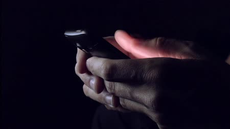 сообщение : Man sending SMS text message on smartphone in dark room, close up of hands and mobile phone Стоковые видеозаписи