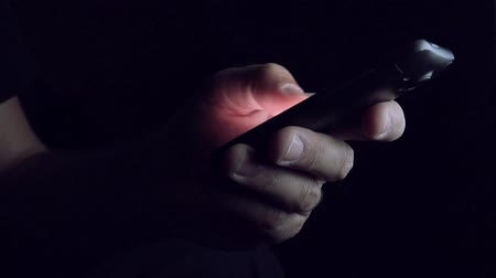 текст : Man sending SMS text message on smartphone in dark room, close up of hands and mobile phone Стоковые видеозаписи