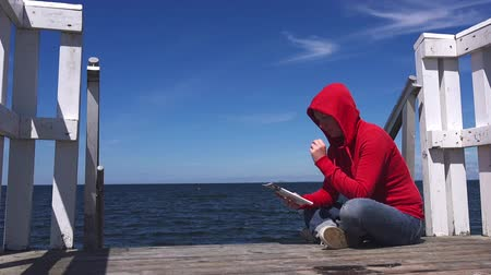 časopis : Young woman reading fanzine magazine at the edge of wooden ocean pier.