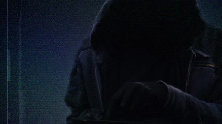 przestępca : Unrecognizable faceless hooded cyber criminal using digital tablet computer to access internet web page, p2p and piracy concept