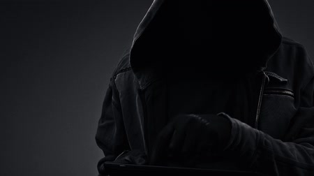 maska : Unrecognizable faceless hooded cyber criminal using digital tablet computer to access internet web page, p2p and piracy concept