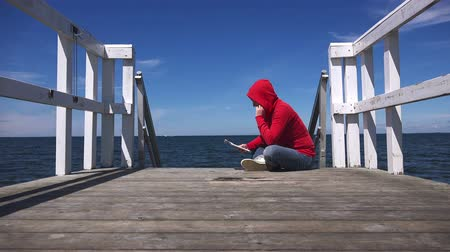 časopis : Young woman reading fanzine magazine at the edge of wooden sea pier, urban lifestyle youth, 4k uhd footage, 3840x2160 Dostupné videozáznamy