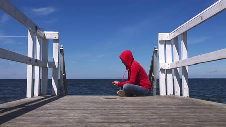juventude : Young woman texting with mobile smart phone at the edge of wooden ocean pier, youth lifestyle communication concept, 1920x1080 full hd footage.