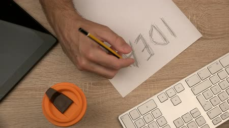 escrever : Graphic designer writing idea on piece of paper with felt pen marker, office desktop top view, tabletop in design studio, workspace from above, fast motion time lapse, point of view pov 4k uhd footage 2160p.