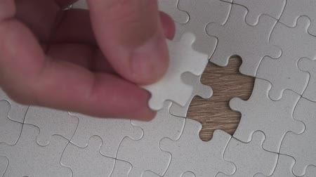 кусок : Male hand putting a missing piece and solving blank white jigsaw puzzle, 4k uhd footage, 2160p, 3840x2160 Стоковые видеозаписи