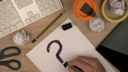 inspiração : Businessman sketching question mark at office workspace, office table top view.