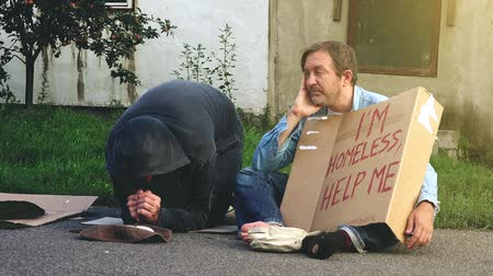 segít : Man on the street giving change money to homeless people begging on the street, 4k uhd footage Stock mozgókép