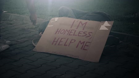 evsiz : People giving money to homeless beggar sleeping on the street, adult man begging down on pavement