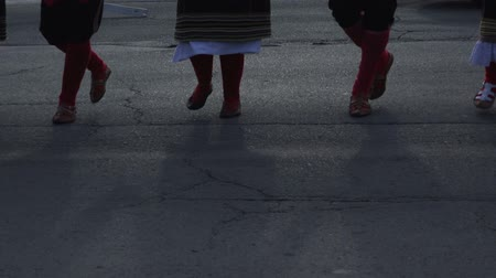 sérvia : Kolo - people dancing Serbian folk dance, focus on legs and shadows on the pavement