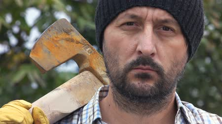 komoly : Serious confident lumberjack, adult bearded man holding a big axe and looking at camera in outdoors surrounding, close up of face, treetop in background.