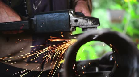 измельчение : Metal worker grinding steel pipe, adult man using grinder to work on piece of metal in workshop, grinding sparks flying around, handheld camera with tracking focus