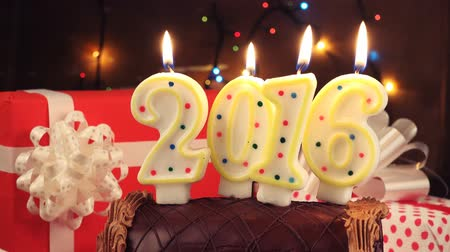 família : Happy New 2016 Year, romantic candle light with chocolate cake and magical gift boxes as holiday season background. Vídeos