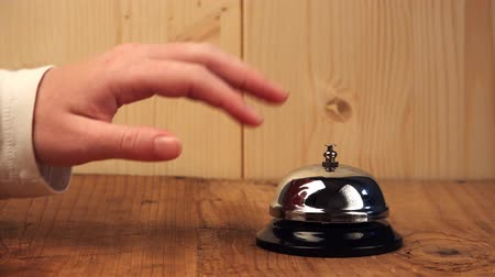 szállás : Nervous woman ringing hotel reception bell, female hand pushing accommodation call bell on wooden reception front desk Stock mozgókép