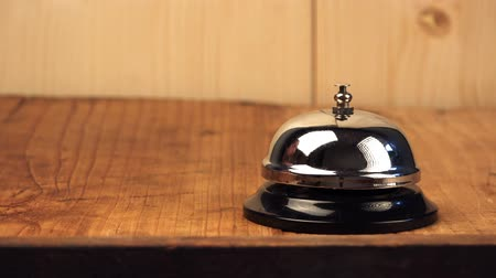 talep : Nervous man ringing hotel reception bell, male hand pushing accommodation call bell on wooden reception front desk