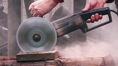cegła : Grinder worker cuts stone block with electric hand saw, focus on tool, 1080p hd footage.