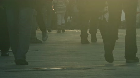 разнообразие : Unrecognizable crowd of people walking on city street in sunset, silhouettes of people and shadows on pavement.