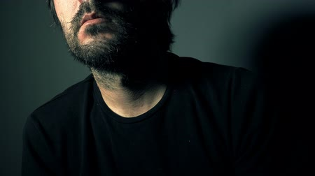 unbalanced : Psychotic bearded man with mental problems, low key portrait in dark room