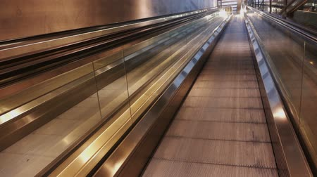gyalogút : Moving walkway or sidewalk ride in modern architectural interior, no people.