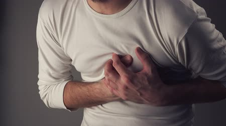 нападение : Man suffering from spasm or chest pain, having severe heart attack or painful cramps, pressing on chest with painful expression.