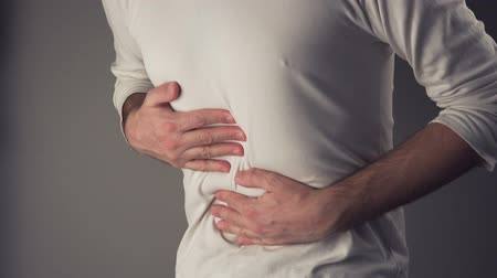 painéis : Man suffering from stomach ache, severe abdominal pain, holding his belly and having painful cramps. Stock Footage