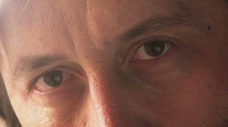 olhos castanhos : Close up footage of sad adult male eyes, man standing by the window and thinking.