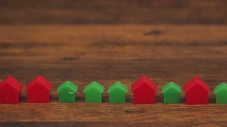 architecture and urbanism : Miniature plastic houses on wooden table as mortgage concept, dolly slider camera slow motion Stock Footage