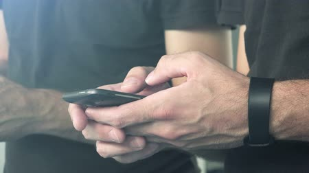 текст : Casual man using smart phone to send text message, male hands holding mobile telephone device Стоковые видеозаписи