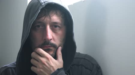 решение : Depressed man in hooded jacket looking at camera, hand on chin as body language or making tough decisions or judgment.