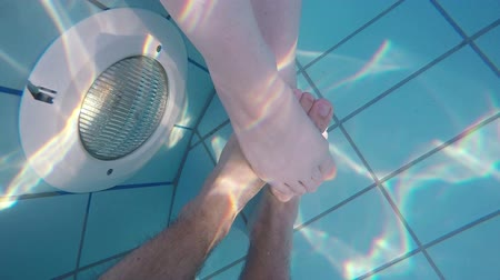 прижиматься : Feet of adult caucasian couple touching gently in outdoor swimming pool water, underwater slow motion shot