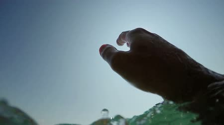 kézi : Man drowning in the sea, hand asking for help sticking out of cold water with air bubbles, pov shot