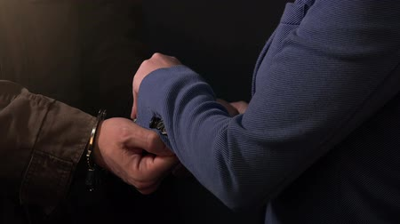 restraining : Female detective arresting and handcuffing criminal, police procedure for taking suspect person into custody Stock Footage