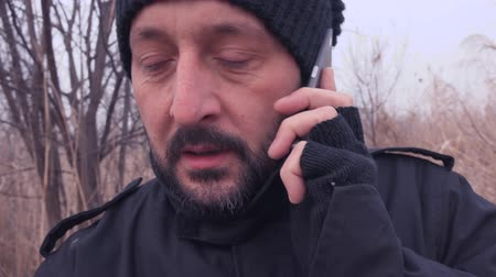 bağlantılı : Unshaven man walking through countryside and talk on mobile phone on cold winter afternoon