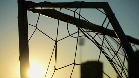 göller : Soccer goalpost and net on practising pitch as abstract sport and football background, late afternoon sunlight, handheld camera Stok Video