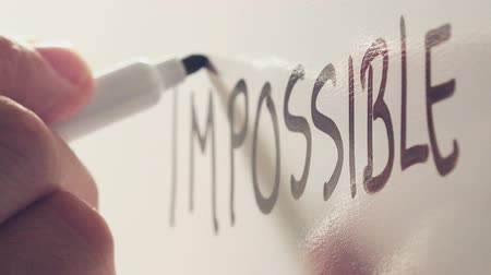 olasılık : Businessman changing word Impossible to Possible on office whiteboard with marker felt pen