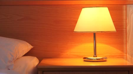 szállás : Light lamp on night table in hotel room next to the empty bed and pillow