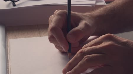 blokkok : Male author suffering from writers block, close up of hands with pencil