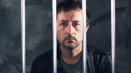 trest : Man behind prison bars. Arrested criminal male person imprisoned. Dostupné videozáznamy