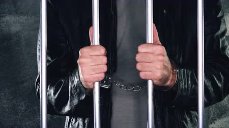 restraining : Man behind prison bars. Arrested criminal male person imprisoned. Stock Footage
