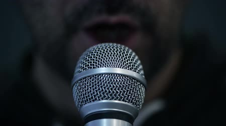 publicity : Man speaking to microphone in dark room